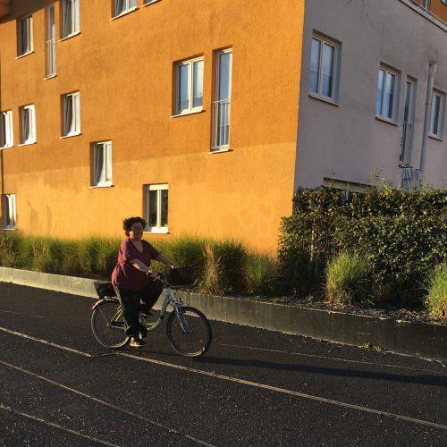 Sabine auf dem Rad in der Abenddämmerung vor einem orangen Haus